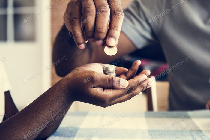 Dad giving coins to his daughter