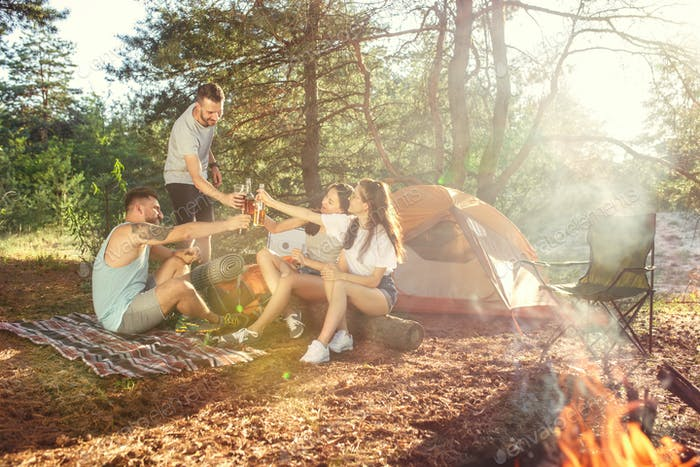 Party, camping of men and women group at forest. They relaxing