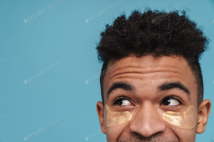 Photo of african american man with under eye patches looking upward