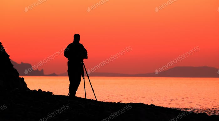 Silhouette of a male photographer by the sea