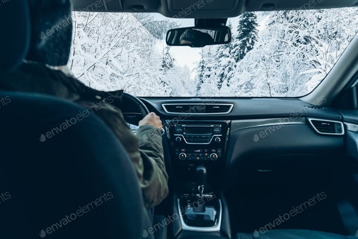 Man drives a car on snow winter road.