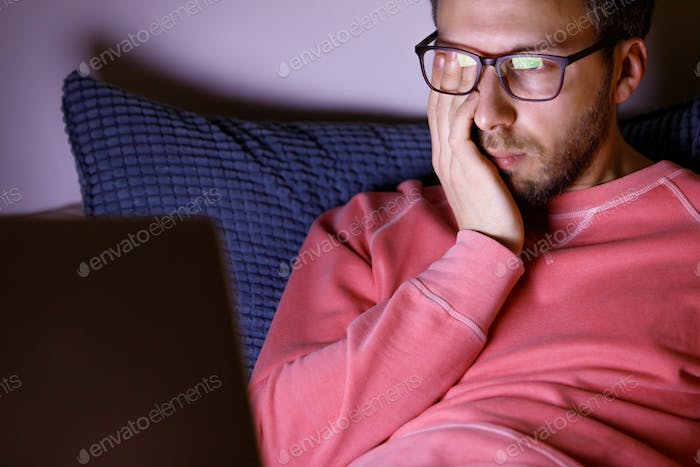 Sleepy man in glasses rubbing his eyes, feels tired after working on a laptop