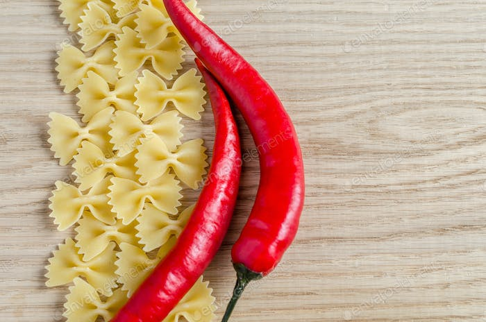 Uncooked farfalle pasta and chili peppers