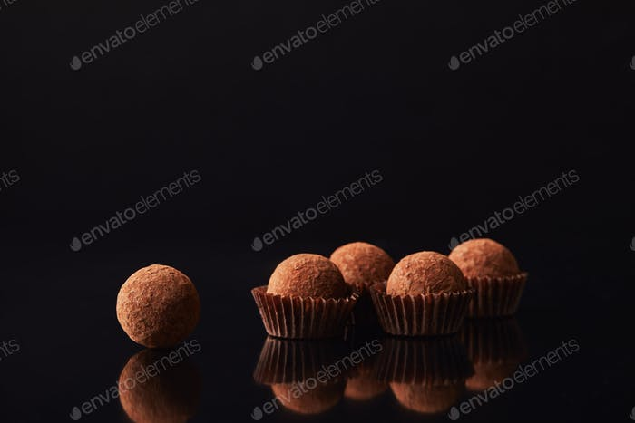 close up view of tasty truffles on black