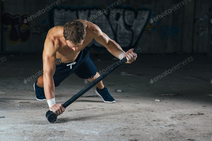 Sportsman doing push ups with sledgehammer