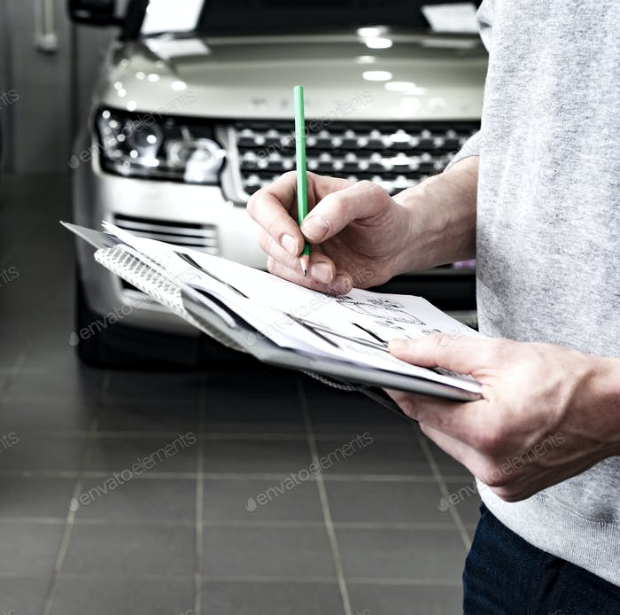 Mechanic writing to the clipboard at workshop warehouse