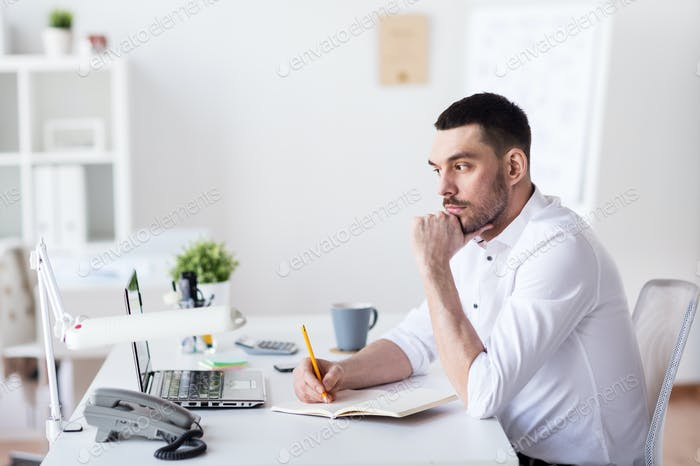 businessman with laptop and notebook at office