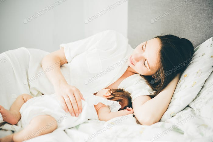 Young mother breastfeeds her baby girl at home.