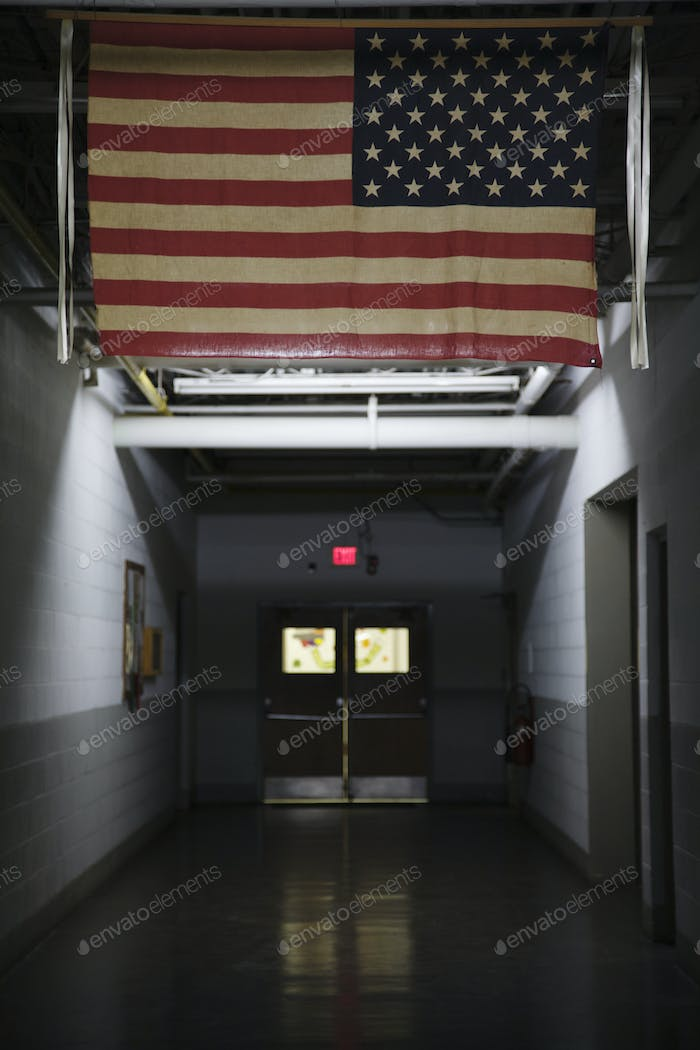 51890,An American flag, the stars and stripes hanging in a public place, in a corridor.