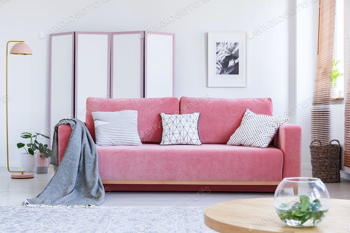 Real photo of a pink couch with white pillows and a blanket stan