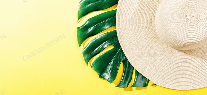 Straw hat on bright yellow sunny background