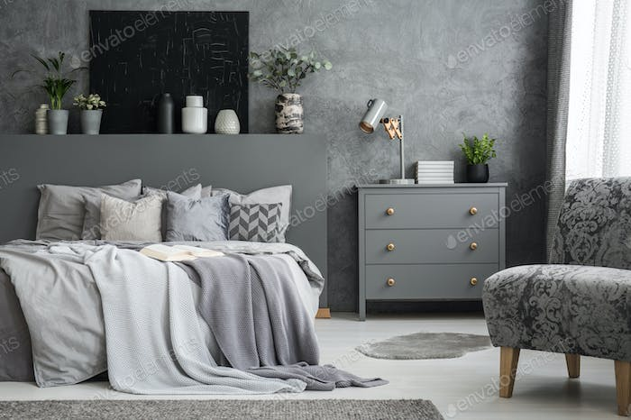 Grey armchair near cabinet and bed with sheets in bedroom interi
