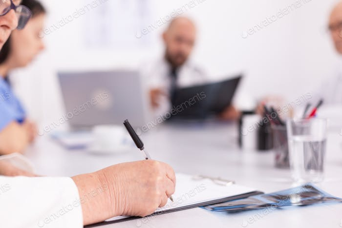 Close up of unknown doctor taking notes