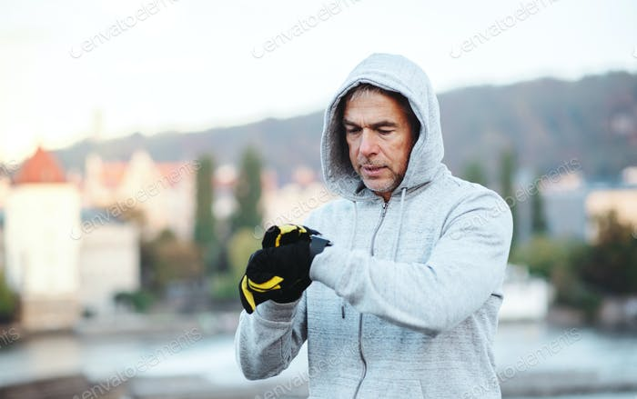Mature male runner standing outdoors in city, resting and checking the time.