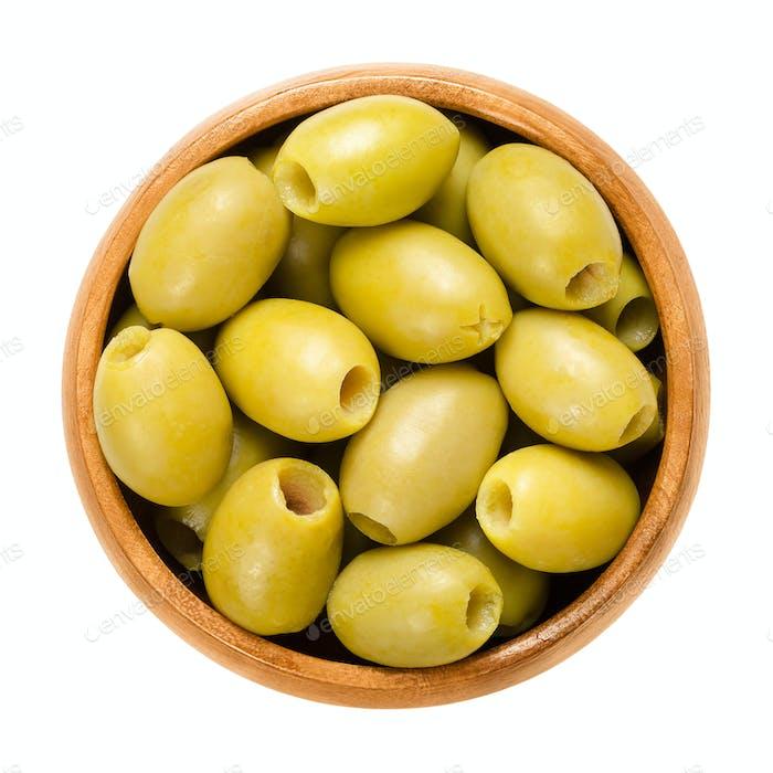 Entsteinte und marinierte grüne Oliven in Holzschale