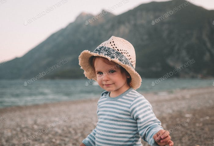 Cute little baby girl in hat playing on a beach in summer day. Family Travel and vacation concept