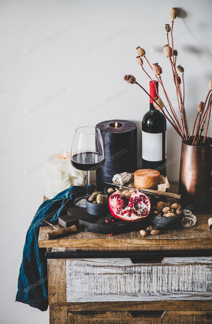 Red wine and snacks over rustic wooden kitchen counter