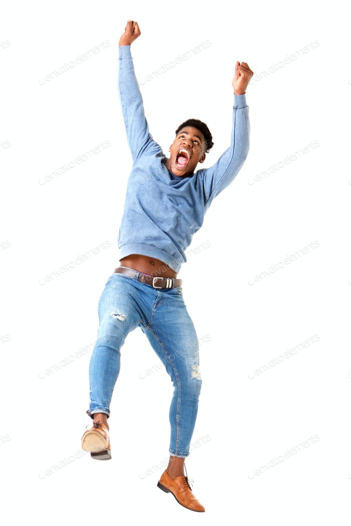 Full body cheerful young black man jumping with arms raised against isolated white background