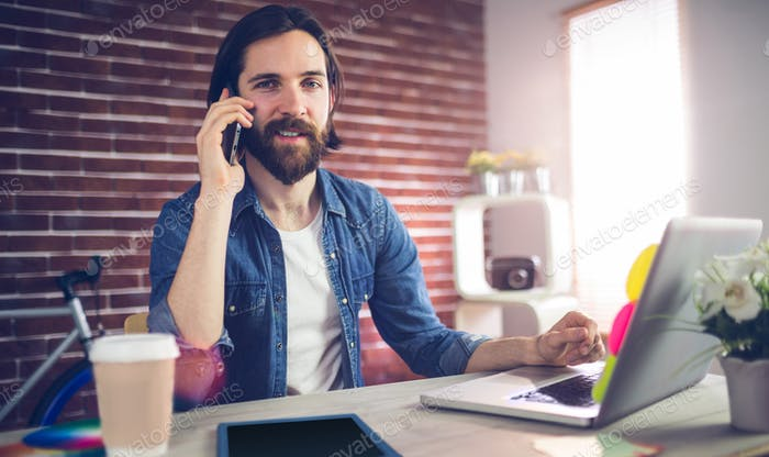 Portrait businessman talking on the phone in creative office