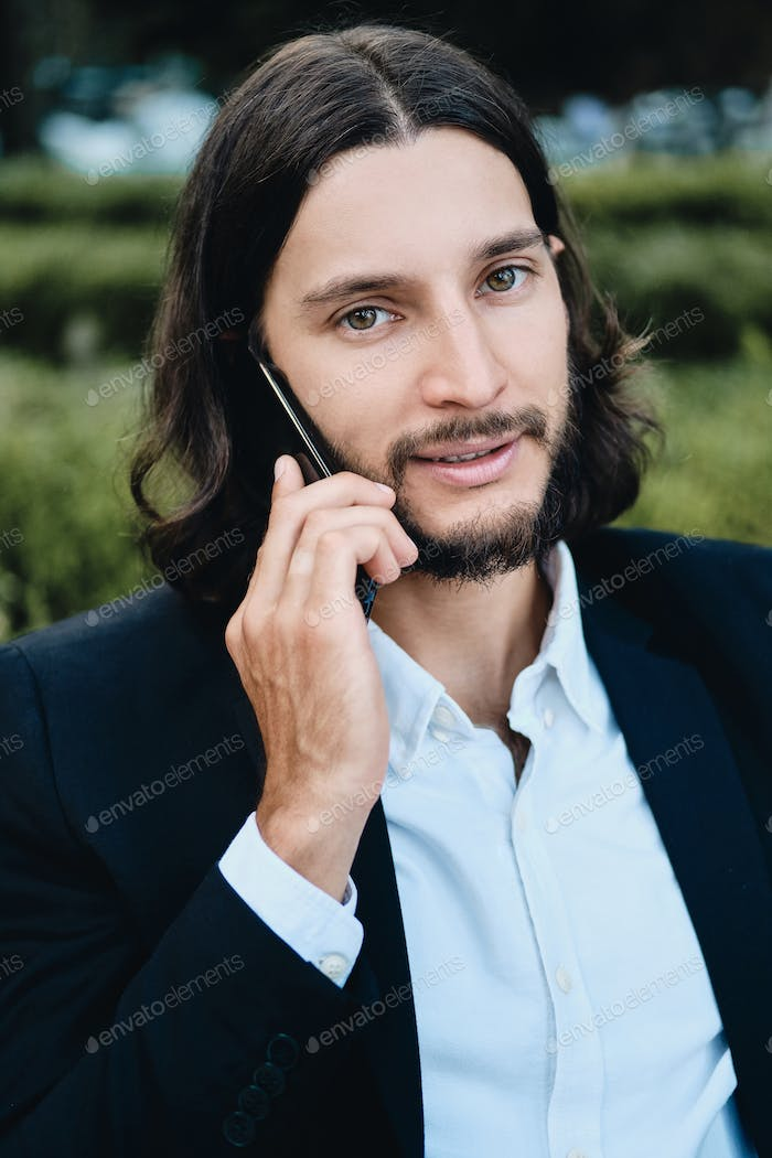 Attractive confident latin businessman looking in camera talking on cellphone in restaurant outdoor