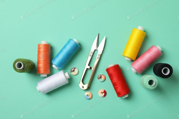 Sewing supplies on mint background, top view