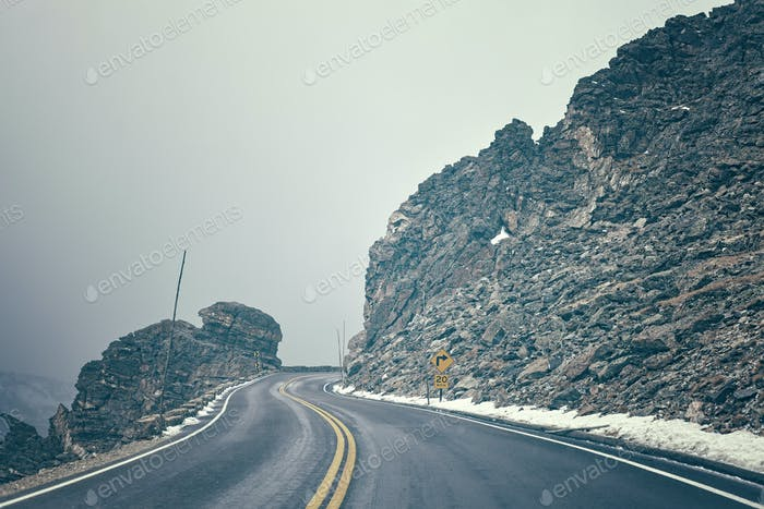 Retro color toned mountain road in fog.