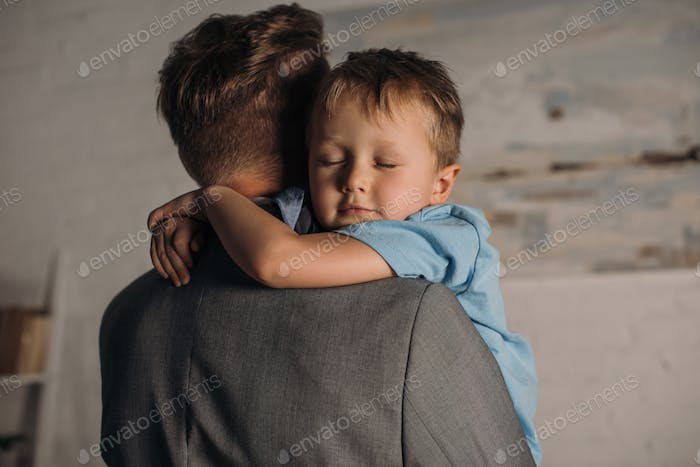 little boy with eyes closed hugging father at home
