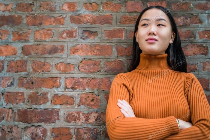 Asiatische Frau gegen Ziegelmauer.