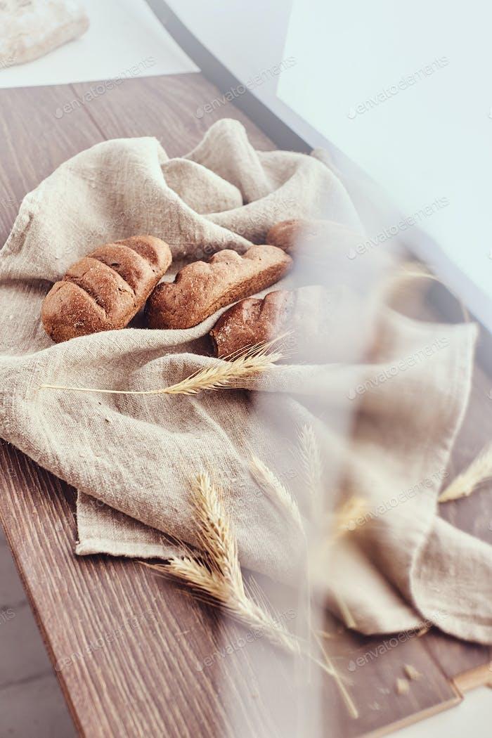 Frisch gebackene Brötchen und Ährchen Weizen auf einem Leinentuch liegen.