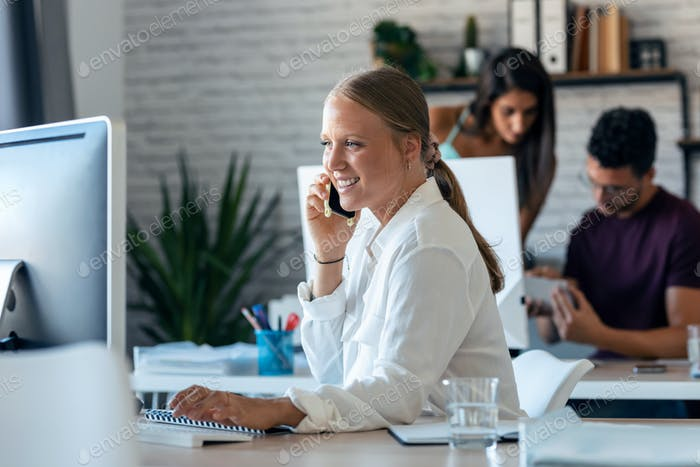 Smart businesswoman talking on mobile phone while working with her computer in the office.