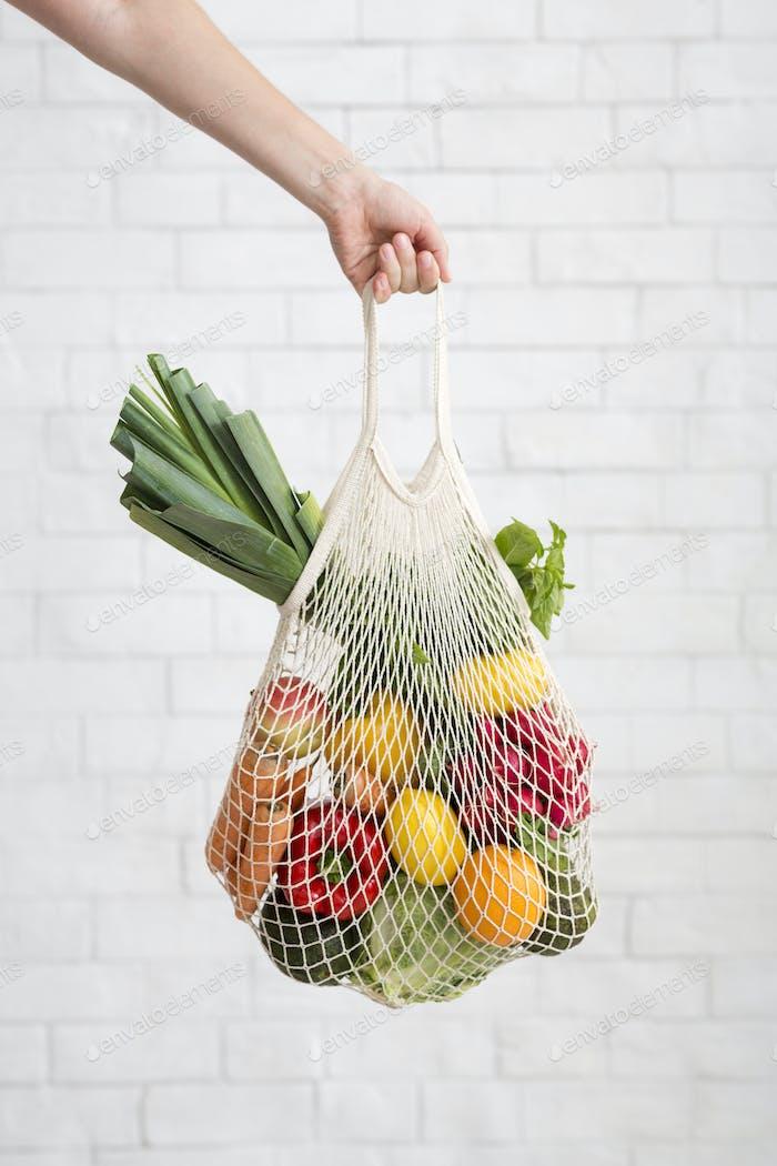 Frau hält Mesh-Einkaufstasche mit bunten Gemüse