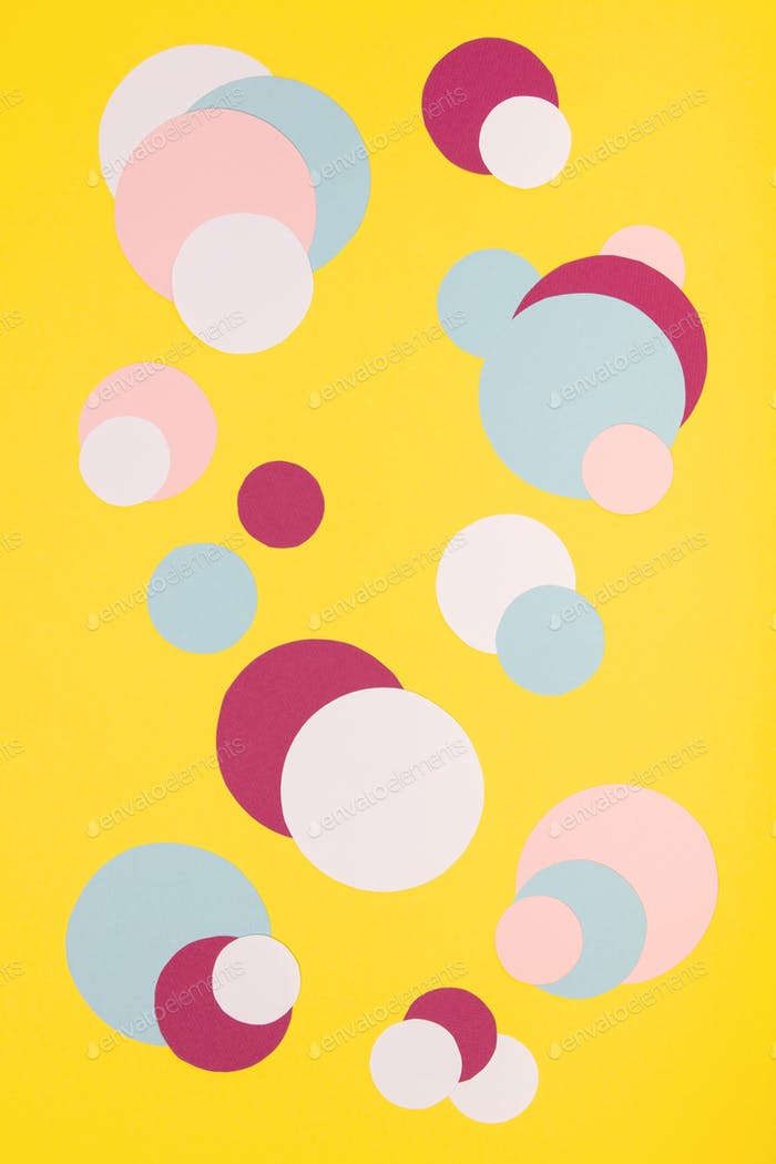 Colorful paper circles on yellow paper background