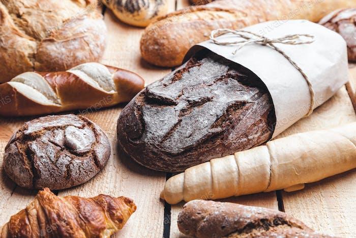 Köstliches frisches Brot auf hölzernem Hintergrund