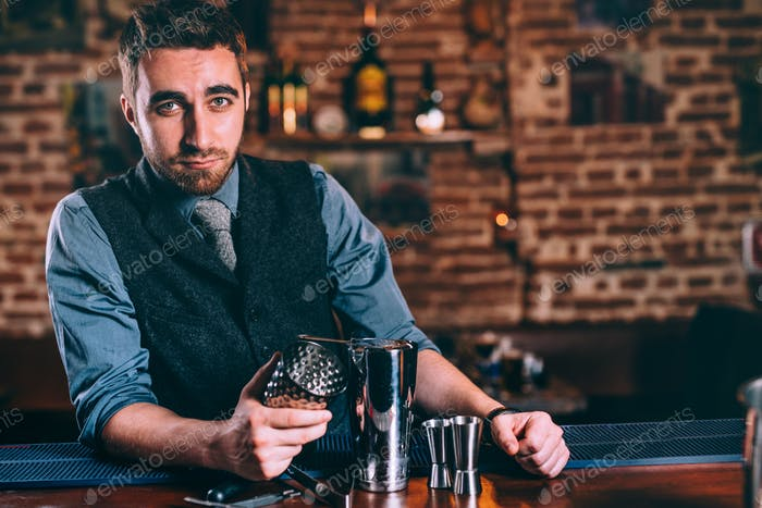 Professional bartender making cocktails at restaurant or bar. Portrait of stylish barman in bar