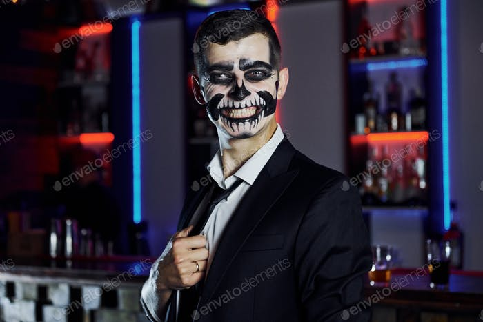 Portrait of man that is on the thematic halloween party in scary skeleton makeup and costume