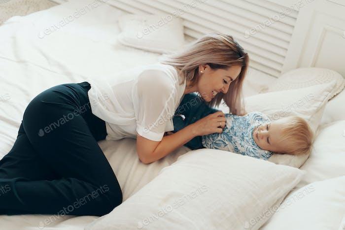 Junge Mutter mit Spaß lachen spielen lustige aktive Spiele mit niedlichen Kind Sohn im Schlafzimmer