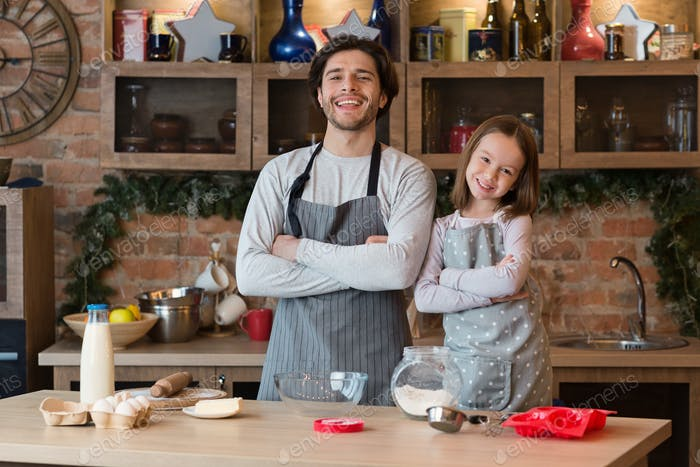 Home Bakers. Happy Dad And Little Daughter Posing In Aprons At Kitchen