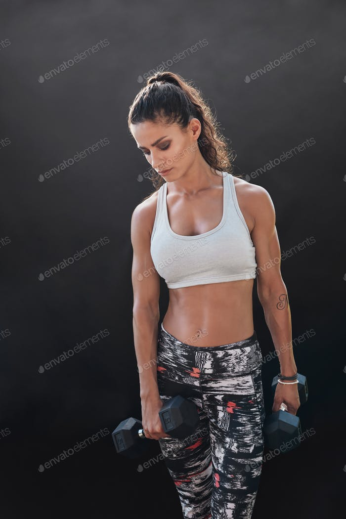 Bodybuilding model exercising with heavy dumbbells