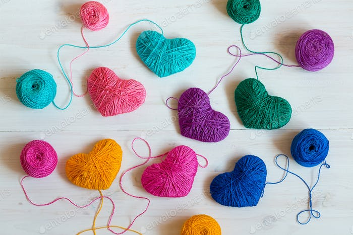 Multicolored Hearts with a balls of thread on white wooden backg