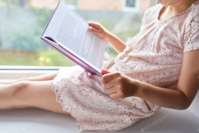 Niedliches kleines Mädchen Lesebuch zu Hause, auf der Fensterbank