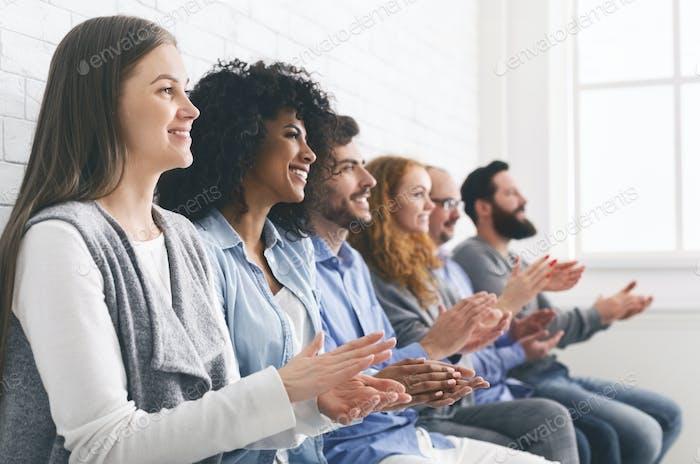 Glückliche Leute sitzen in Reihe applaudieren zu Mentor bei Gruppentherapie