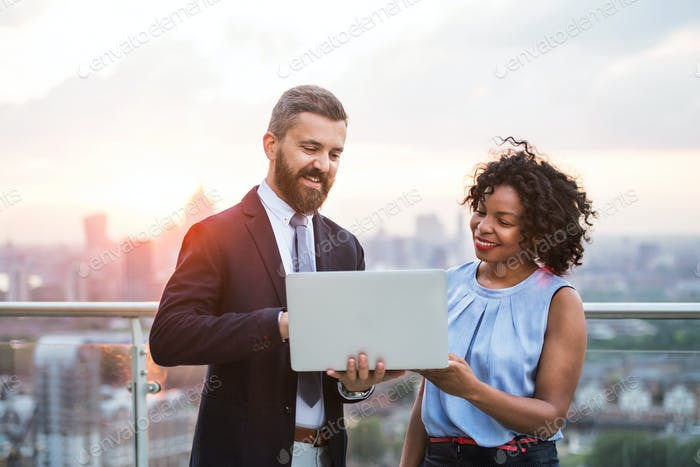 A portrait of businesspeople with laptop standing against London sunset view.