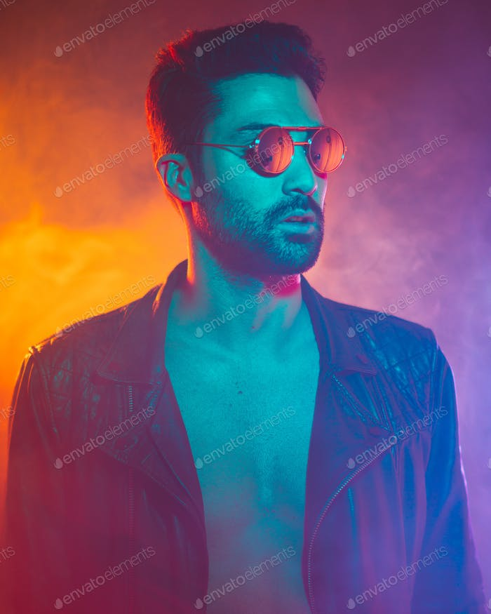 Cinematic portrait of Handsome man with sunglasses and neon lights