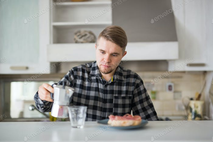 Young man smiling and holding a cup of coffee in kitchen