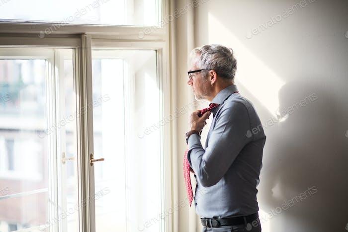 Reifer Geschäftsmann auf einer Geschäftsreise stehen in einem Hotelzimmer, sich anziehen.