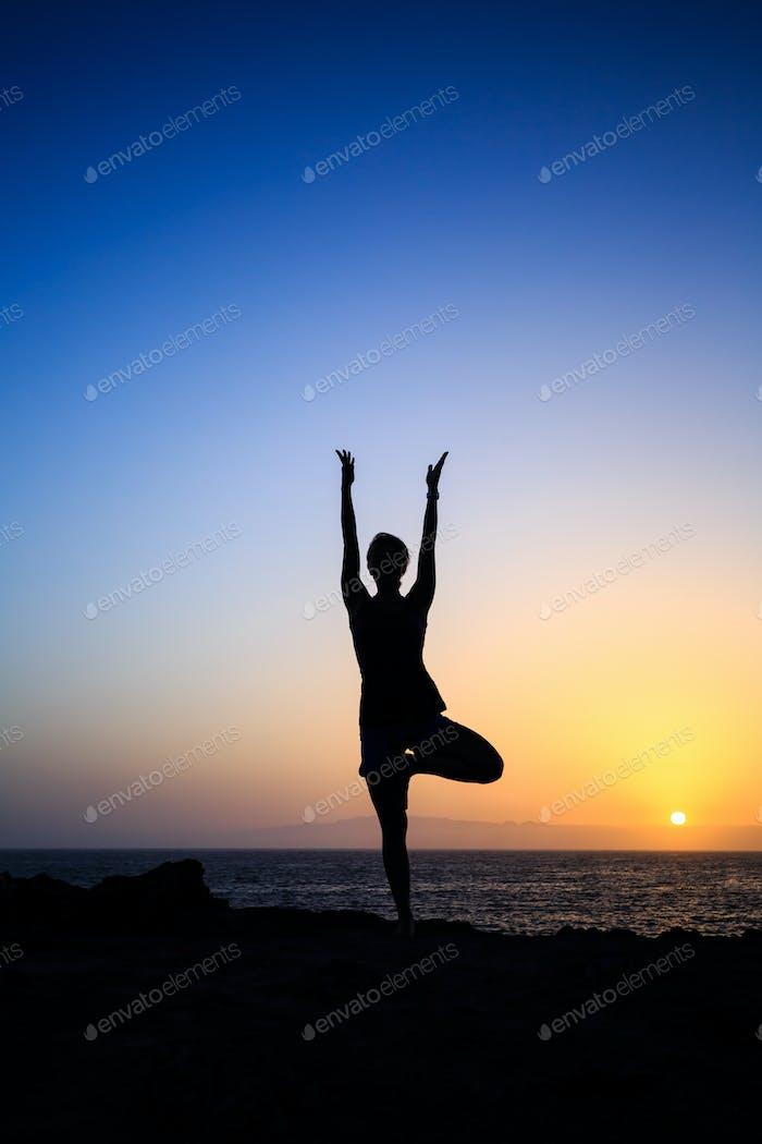 Woman exercising yoga sunset silhouette