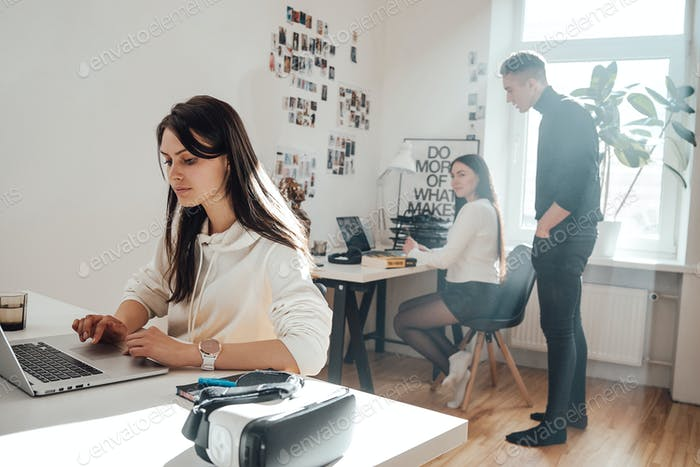 Focused businesswoman types on laptop in comfortable office