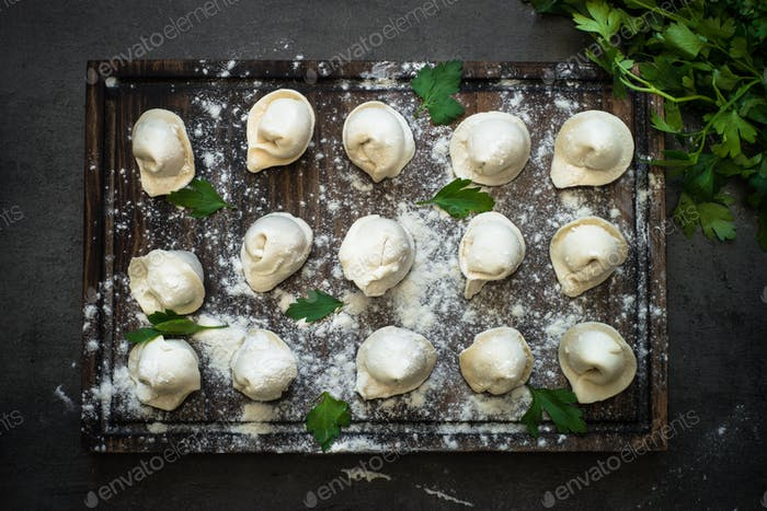 Traditional pelmeni or dumpling at cutting board.