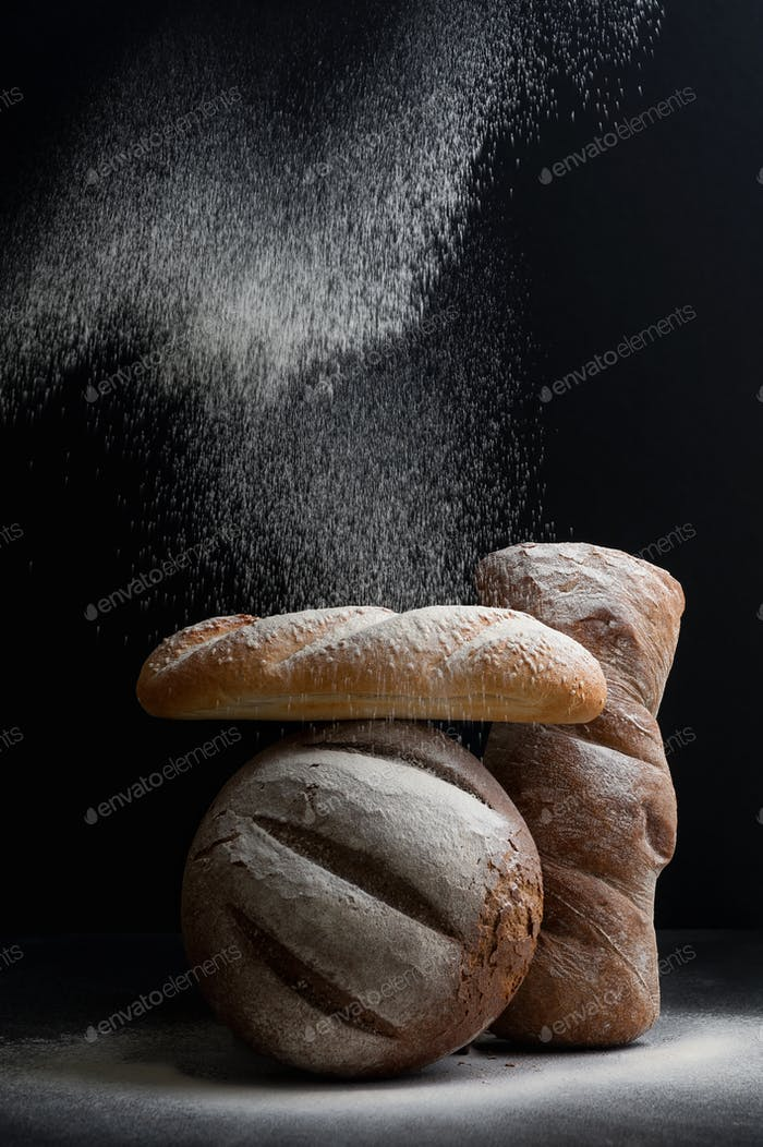 Freshly baked different bread on a black background, on which fl