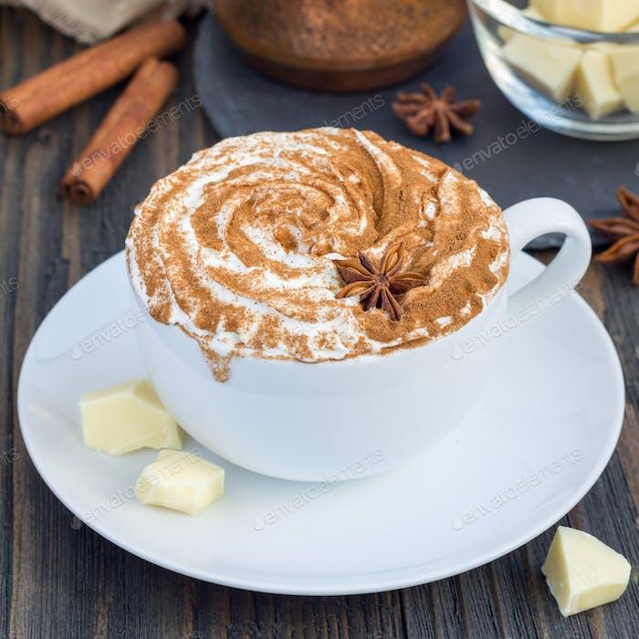 Heiße weiße Schokolade, dekoriert mit Schlagsahne und Zimt, quadratisch